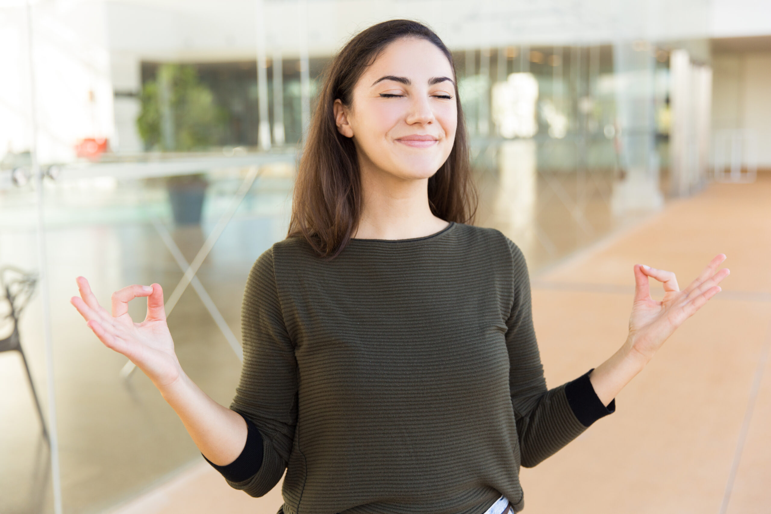 Peaceful smiling beautiful woman making zen gesture with hands. Young woman in casual posing indoors with glass wall interior in background. Stress relief concept